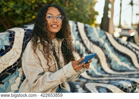 Young latin woman smiling happy using touchpad sitting on the bench at the city.