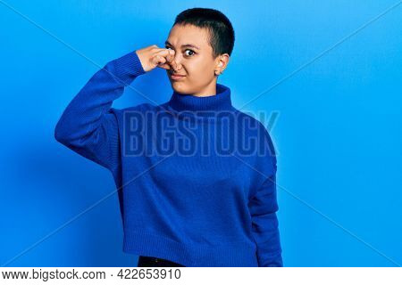 Beautiful hispanic woman with short hair wearing turtleneck sweater smelling something stinky and disgusting, intolerable smell, holding breath with fingers on nose. bad smell