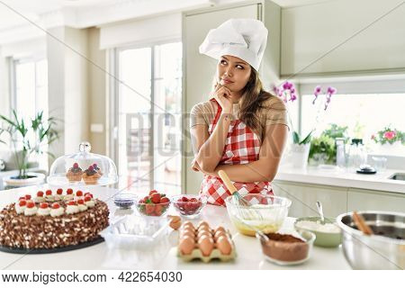 Beautiful young brunette pastry chef woman cooking pastries at the kitchen with hand on chin thinking about question, pensive expression. smiling with thoughtful face. doubt concept.
