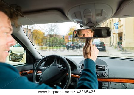 Experienced taxi driver is looking in the rear view mirror in his taxi, he sets the taximeter