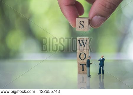 Hand Putting Wooden Cube Of S On W, O, T Beside Miniature People Businessman Meeting. Swot Abbreviat
