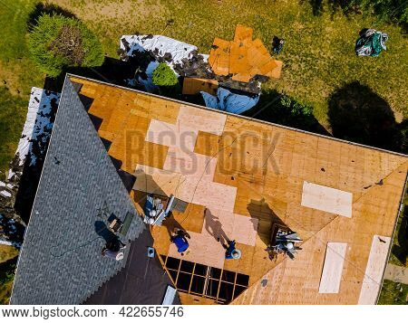 Aerial View Of Roof Construction Repairman On A Residential Apartment With New Roof Shingle Being Ap