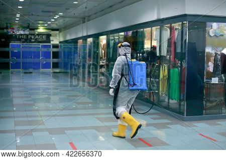 Labuan,malaysia-may 6,2021:worker In Personal Protective Equipment Spray Disinfectant To Prevention
