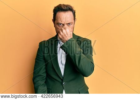 Middle age man wearing business suit smelling something stinky and disgusting, intolerable smell, holding breath with fingers on nose. bad smell