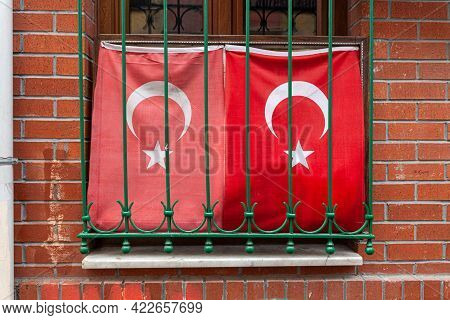 Two Waving Turkish Flag In Window With Grate, Brick Wall