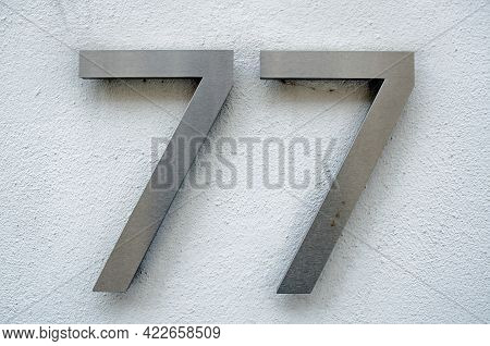 Brushed Metal Figures For The Number Seventy Seven On A Rough, White Painted Wall On The Outside Of