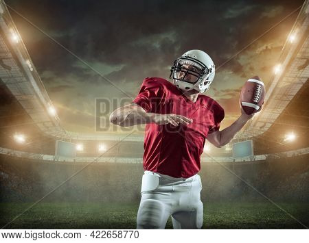 American football sportsman player with ball in action on stadium under lights of background. Sport, proud footballer in white helmet and red ready to play.