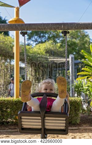 Mackay, Queensland, Australia - June 2021: A Young Female Child Enjoying A Swing In The Playground