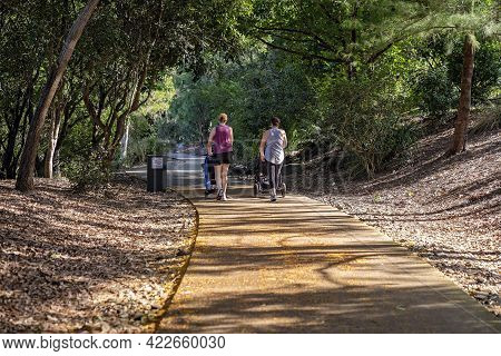 Mackay, Queensland, Australia - June 2021: Two Mothers Pushing Prams With Their Children As They Exe