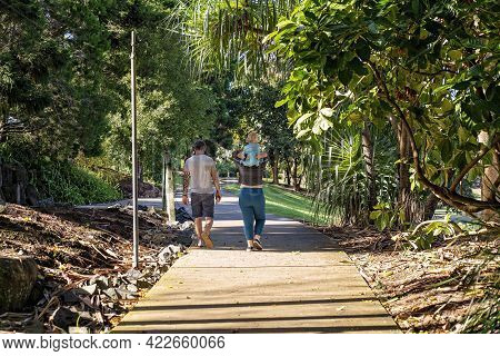 Mackay, Queensland, Australia - June 2021: Couple Walking In The Botanic Gardens With Their Young Ch