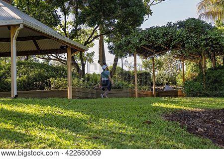 Mackay, Queensland, Australia - June 2021: Woman Walking For Exercise In The Public Botanic Gardens
