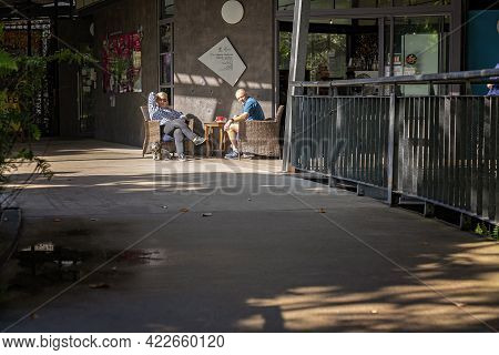 Mackay, Queensland, Australia - June 2021: An Older Couple Relax With Their Dog In The Sun At A Coff