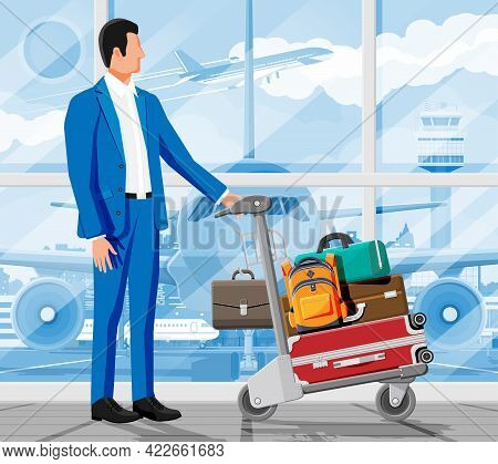 Man And Hand Truck Full Of Bags In Terminal Interior. Glass Window Airfield. Airport Luggage Trolley