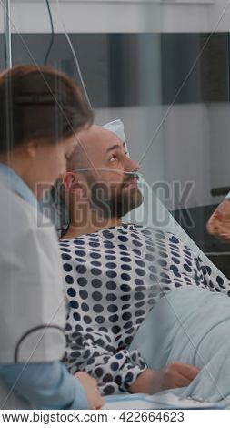 Patient Discussing With Doctors While Lying In Bed During Sickness Recovery In Hospital Ward. Practi