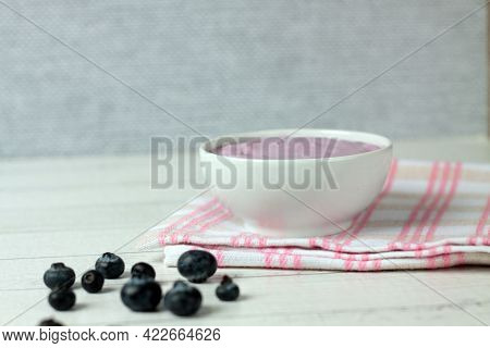 Healthy Eating Concept - A Bowl Of Blueberry Yoghurt And A Pile Of Berries On A Napkin Against Light