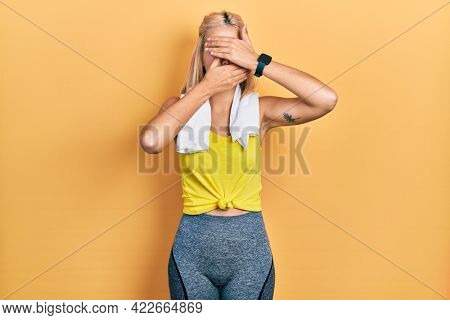 Beautiful blonde sports woman wearing workout outfit covering eyes and mouth with hands, surprised and shocked. hiding emotion