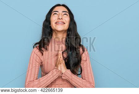 Hispanic teenager girl with dental braces wearing casual clothes begging and praying with hands together with hope expression on face very emotional and worried. begging.
