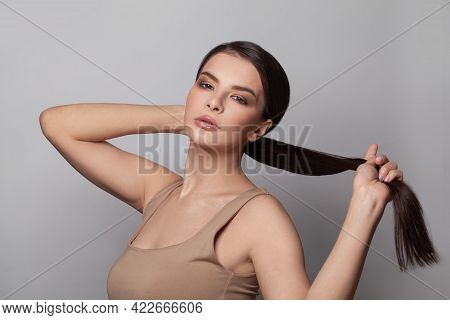 Beautiful Young Woman Touching Her Ponytail Hairstyle With Smooth Straight Hair