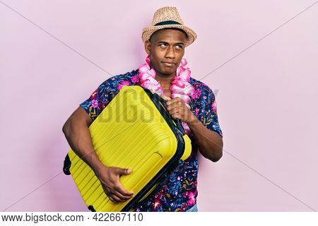Young black man wearing summer hat holding cabin bag smiling looking to the side and staring away thinking.