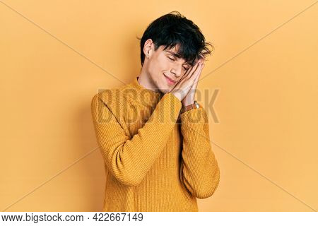 Handsome hipster young man wearing casual yellow sweater sleeping tired dreaming and posing with hands together while smiling with closed eyes.