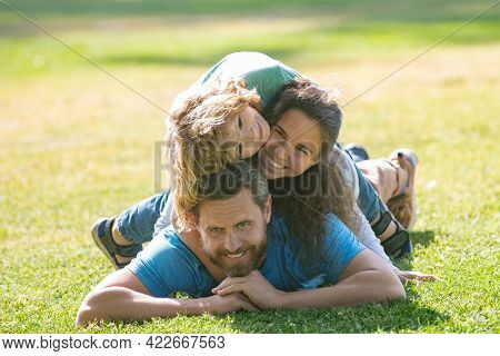 Happy Family Hugging And Embracing On Summer Walk. Father Mother And Child Walking In The Park And E