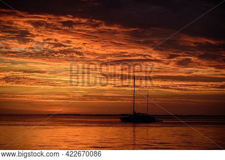 Sailboat On The Sea At Sunset. Boat With Sails. Ocean Yacht Sailing Along Water.