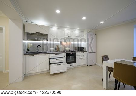 Modern large luxurious white kitchen interior, some drawers pulled out