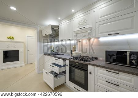 Modern large luxurious white kitchen interior with fireplace, some drawers pulled out