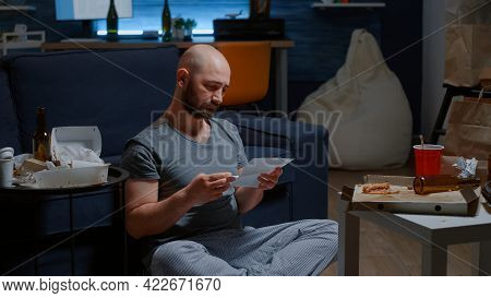 Worried Man Open Warning Document, Reading Letter From Bank About Loan Refusal Sitting On Floor. Dep