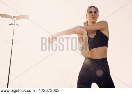 young athletic girl runner doing stretching before jogging.