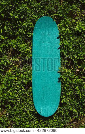 Green Wooden Skateboard On Grass Outdoors On A Sunny Day. Skateboarding Background, Street Extreme S