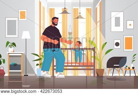 Young Father Playing With Little Son In Crib Fatherhood Parenting Concept Dad Spending Time With His