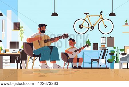 Young Father Teaching Little Son To Play The Guitar At Home Parenting Fatherhood Concept