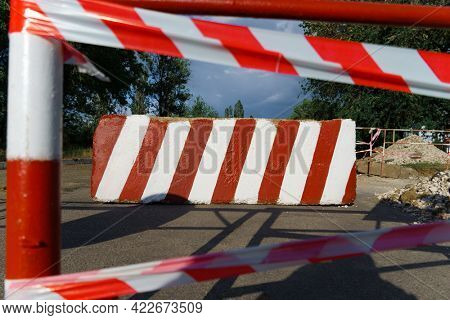 concrete block with red and white striped lines as a roadblock, traffic is prohibited and road works, the road is closed for maintenance