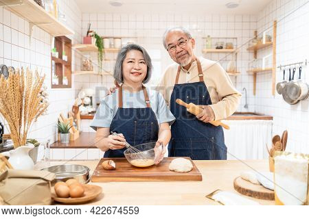 Portrait Of Asian Happy Senior Elderly Couple Standing In Kitchen At House Feel Happy And Enjoy Fami
