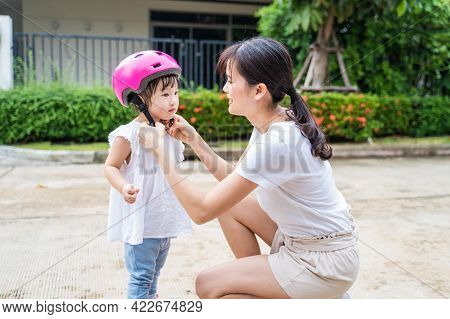 Asian Loving Mother Put On Sport Helmet To Young Little Cute Kid Daughter Before Ride Bicycle For Ex