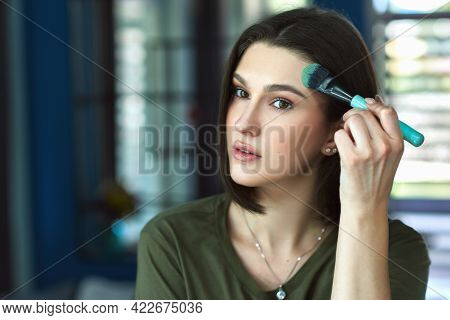 Portrait Of A Beautiful Brunette Young Woman Looking To The Mirror And Making Makeup Herself. Attrac