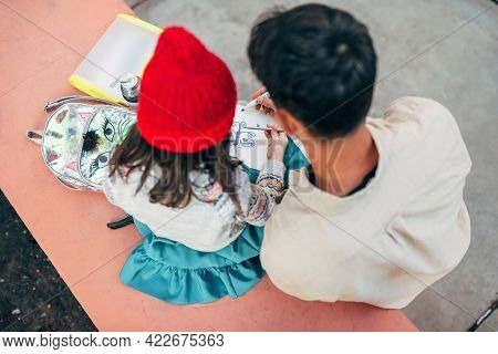Side View Of A Little Girl In Red Hat Drawing With Her Dad Together Outdoors After School. Father En