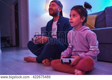 Father And Little Daughter With Gamepads Playing Video Game Together At Home. Dad Plays Computer Gam