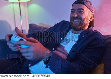 Happy Young Adult Man Gamer Player Holding Gamepad Controller Playing Video Game Sitting Alone On So
