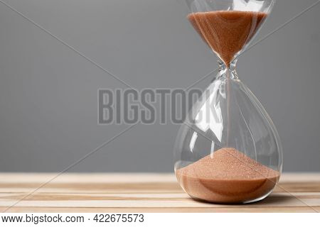 Hourglass On Table Office With Copy Space, Sand Flowing Through The Bulb Of Sandglass Measuring The