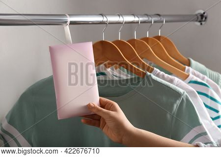 Woman Holding Scented Sachet In Wardrobe, Closeup