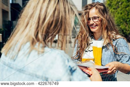 Rearview Of Two Friends Sharing The Books To Each Others On The College Campus Outdoors. Young Femal