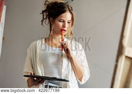 Candid Indoor Portrait Of An Artist Female Standing Next To The Easel With Canvas Painting Something