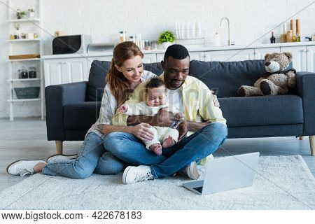 Multicultural Parents With Baby Girl Watching Movie On Laptop On Floor