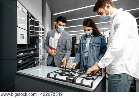 Shop Assistant In Hypermarket Shows New Model Of Gas Stove To Young Couple, All Wearing Medical Mask