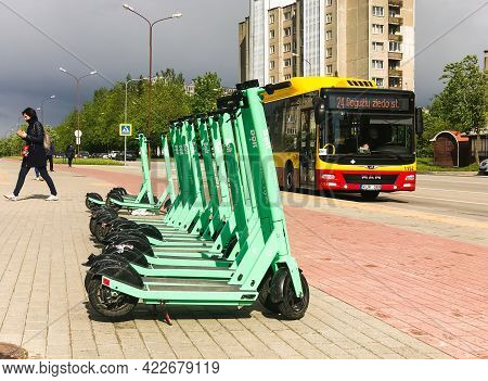 Siauliai, Lithuania - 29th May, 2021: Gren Bol Electric Scooter Standing With Bus And Gil Walking In