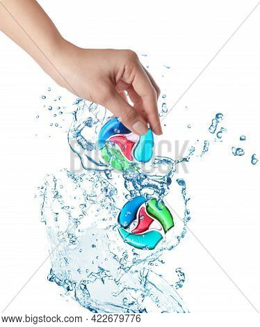 Splashes Of Water And Woman Holding Laundry Capsule On White Background, Closeup. Detergent Pods