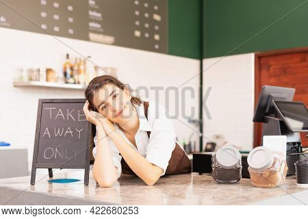 Beautiful Caucasian Barista Woman Happy With Placing Elbows On Table Of Coffee Bar Near Takeaway Sig