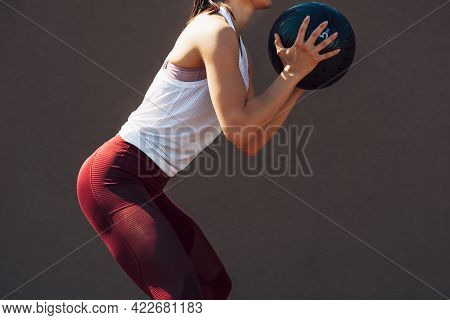 Cropped Image Of A Sporty Young Woman Doing Exercises With A Medicine Ball Outdoors On A Sunny Day.